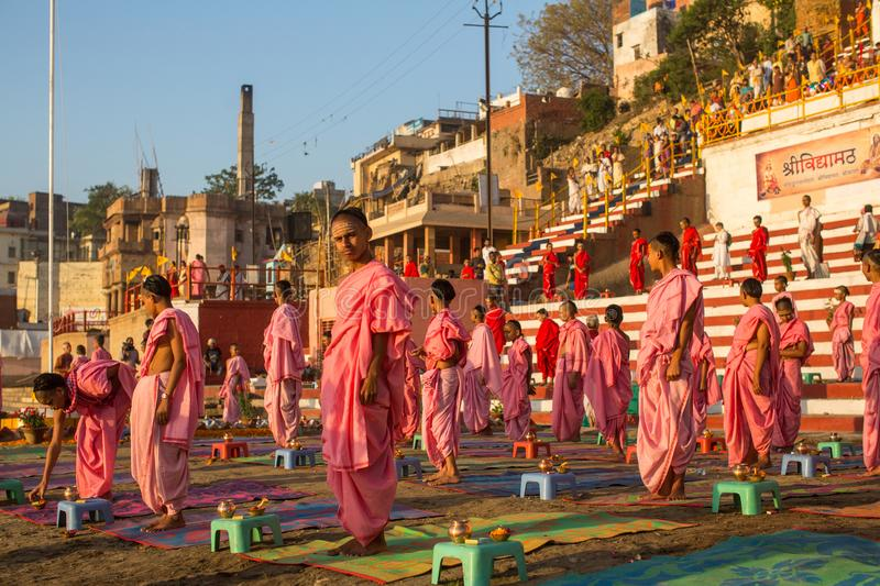 Young hindu monks conduct a ceremony to meet the dawn on the banks of the Ganges. VARANASI, INDIA - MAR 18, 2018: Young hindu monks conduct a ceremony to meet stock images
