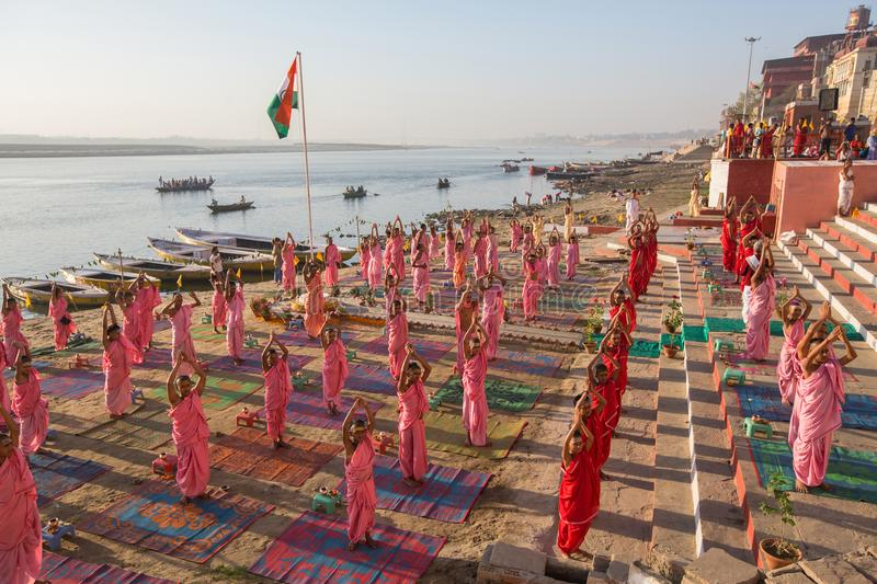 Young hindu monks conduct a ceremony to meet the dawn on the banks of the Ganges. VARANASI, INDIA - MAR 18, 2018: Young hindu monks conduct a ceremony to meet stock photos