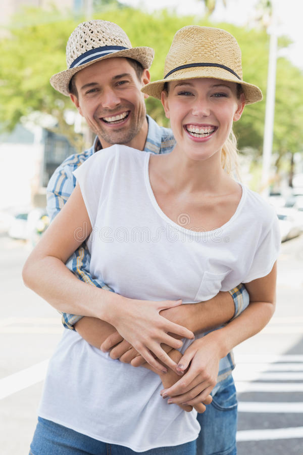 Young hip couple hugging and smiling at camera stock photos