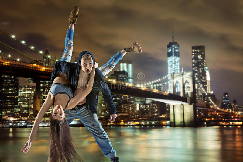 Young hip hop couple dancing, over urban background stock photo
