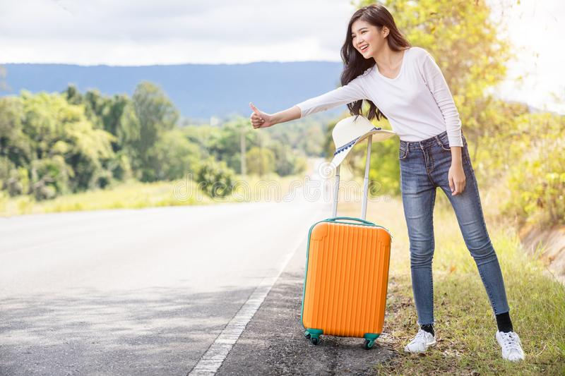 Young hippie woman hitchhiking on the road. Journey travel concept royalty free stock photography