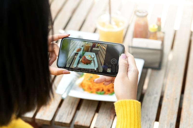 Young hipster asian blogger take photo of food, plate, healthy recipe, lunch meal, breakfast share to story content in social royalty free stock photography