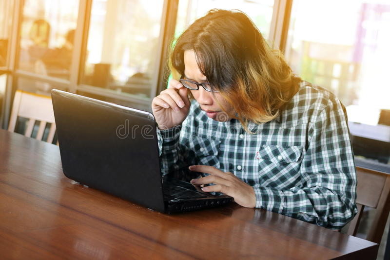 Young hipster Asian businessman looking on laptop for his work with sun flare effect in office background. royalty free stock photography