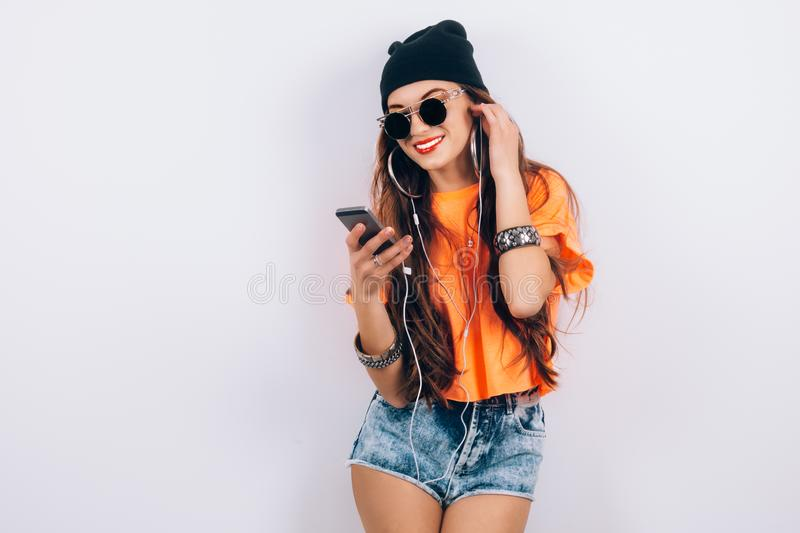 Young hipster beautiful woman in sunglasses wearing in black hat and orange T-shirt listening music in headphones near stock image