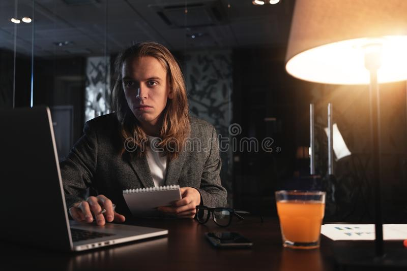 Young hipster businessman sits by the wooden table with lamp, laptop and smartphone at night office. Man with long hair work with stock images