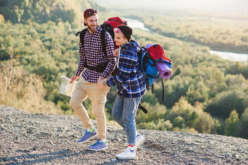Young hipster couple with backpacks hiking in the mountains during long trip. Happy caucasian travelers have amazing stock photo