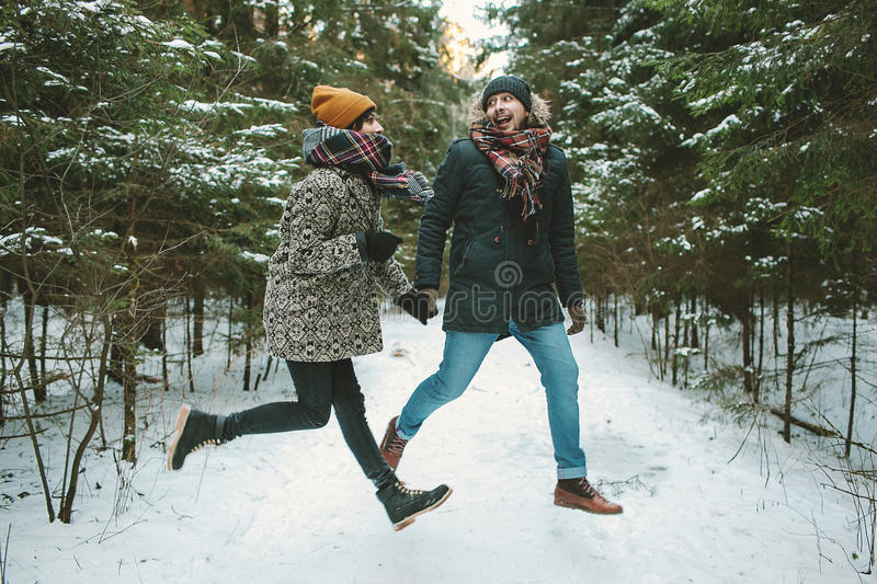 Young hipster couple jumping in winter forest royalty free stock images