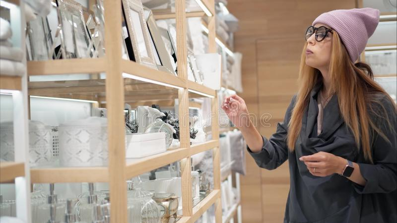 A young hipster female in fashion glasses chooses home acessories in the store. Shopping royalty free stock photography