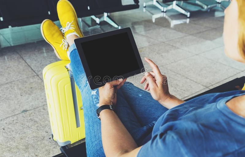 Young hipster girl at airport and put feet in yellow boot on suitcase waiting air flight, female hands holding computer in termina. L departure lounge gate stock photos