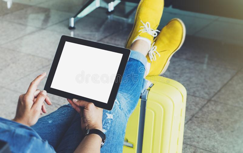 Young hipster girl at airport and put feet in yellow boot on suitcase waiting air flight, female hands holding computer. In terminal departure lounge gate royalty free stock photos