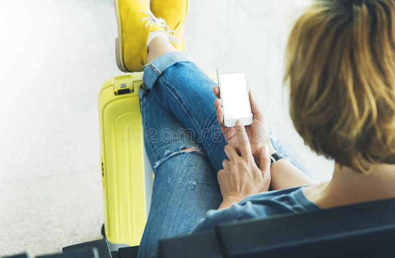 Young hipster girl at airport and put feet in yellow boot on suitcase waiting air flight, female hands holding smart phone. In terminal departure lounge gate royalty free stock images