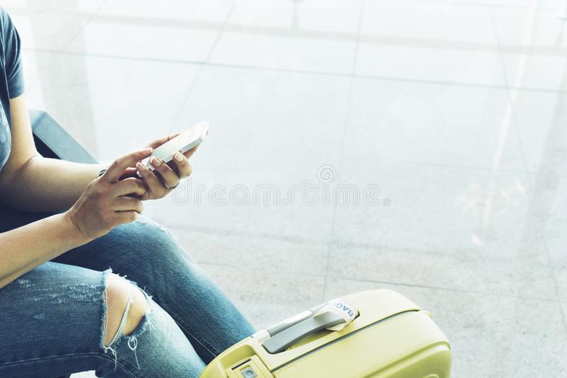 Young hipster girl at airport and put feet in yellow boot on suitcase waiting air flight, female hands holding smart phone. In terminal departure lounge gate royalty free stock photo