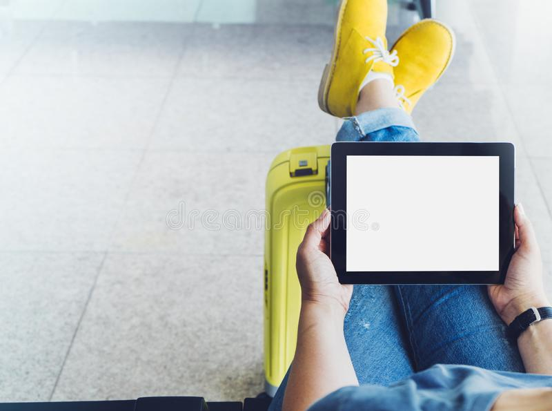 Young hipster girl at airport in yellow boot on suitcase waiting air flight, female hands holding computer in terminal departure. Lounge gate, traveler trip stock image