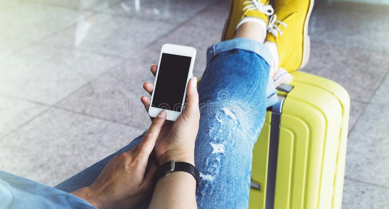 Young hipster girl at airport in yellow boot on suitcase waiting air flight, female hands holding smart phone in terminal departur. E lounge gate, traveler trip royalty free stock images