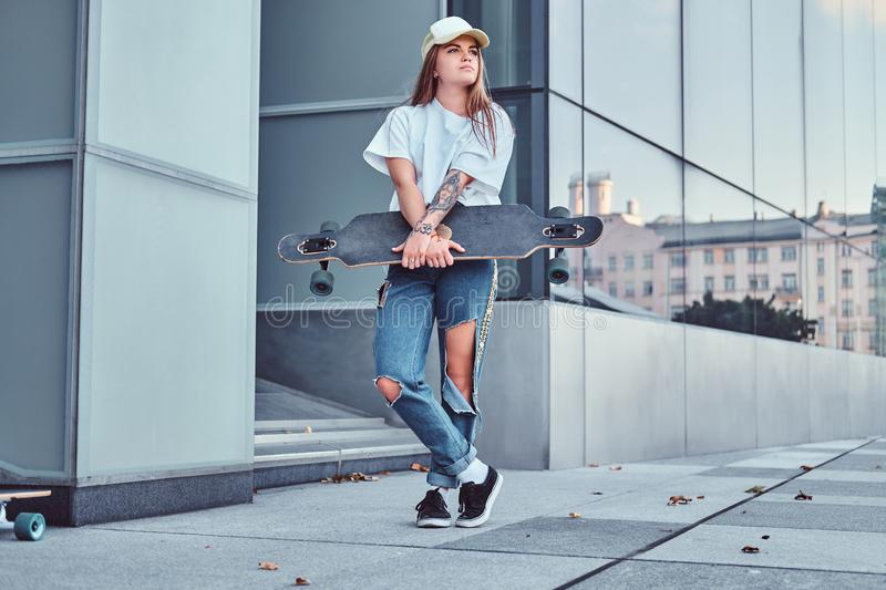 Young hipster girl in cap dressed in a white shirt and ripped jeans holds skateboard while posing near skyscraper. Young hipster girl in cap dressed in white stock photo