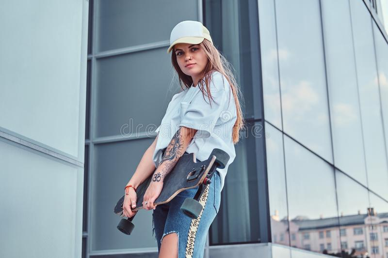 Young hipster girl in cap dressed in a white shirt and ripped jeans holds skateboard while posing near skyscraper. Young hipster girl in cap dressed in white royalty free stock images