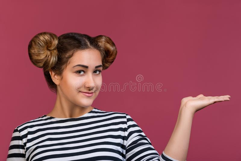 Young girl with funny hairstyle showing open hand palm with copy space for product or text over pink background royalty free stock photo