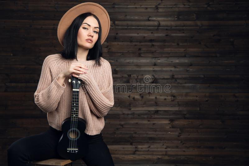 Young hipster girl having fun and posing with small ukulele guitar on a wooden studio background. stock image