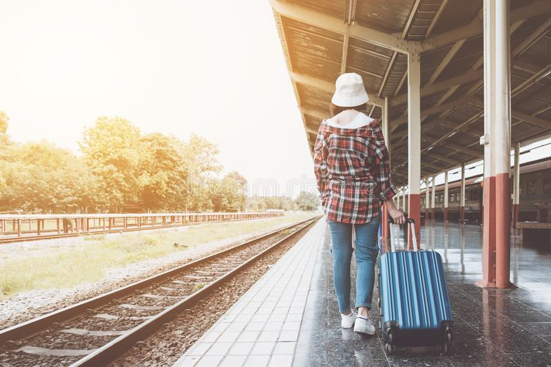 Young hipster girl with luggage at station traveling by train, T stock photos