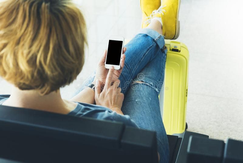 Young hipster girl sitting at airport in yellow boot on suitcase traveling in Europe, female hands texting message on gadget stock photography