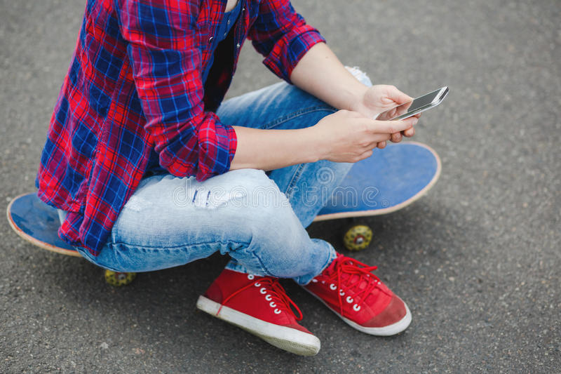 Young hipster girl sitting at skate park and chatting on her phone stock photos