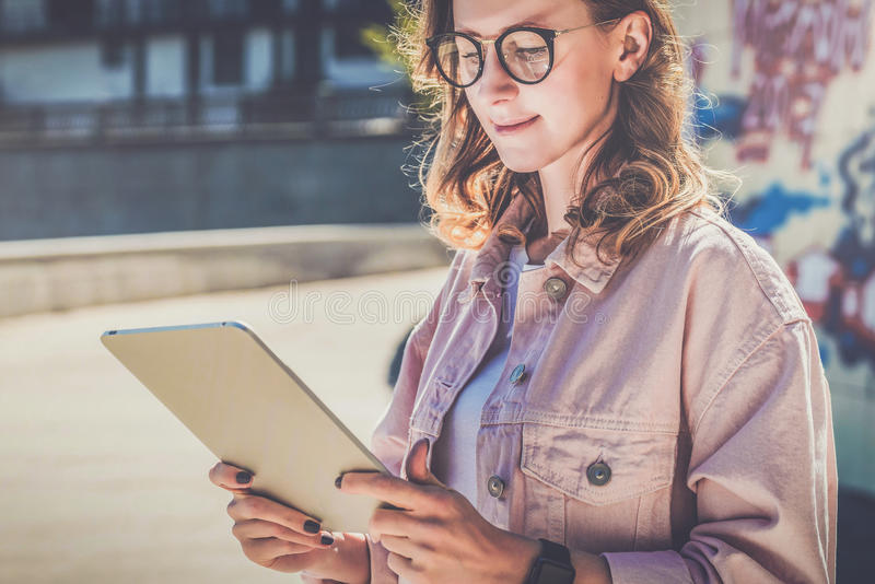 Young hipster woman in glasses stands on city street and uses tablet computer.Girl looking on screen of digital tablet. stock photos