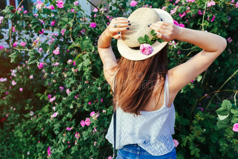 Young hipster girl wearing hat walking by blooming roses. Woman enjoys flowers in park. Summer outfit. stock images