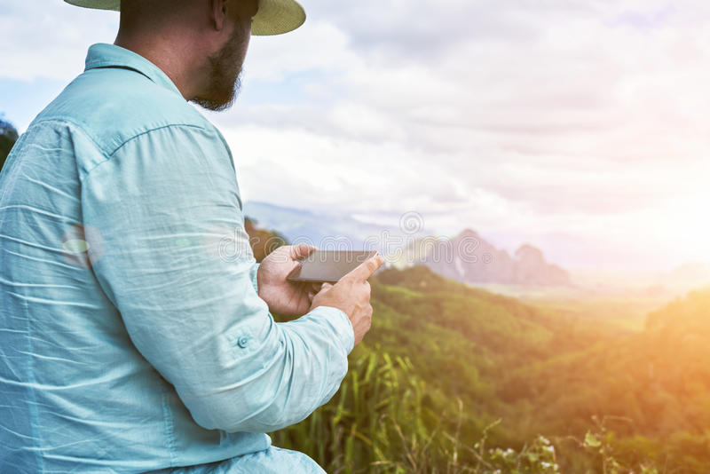 Young hipster guy with cell telephone in hands is enjoying amazing subtropical forest. Closely of a man wanderer is holding mobile phone with copy space on the stock photography