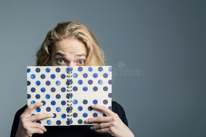 A young hipster guy with long blonde hair covered his face with a paper notebook, big surprised eyes. stock image