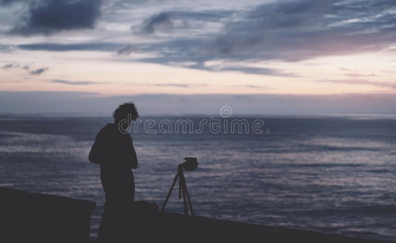 Young hipster guy with long hair takes a picture on photo of a sea sunset at night on a sunset background, silhouette photographer stock photos
