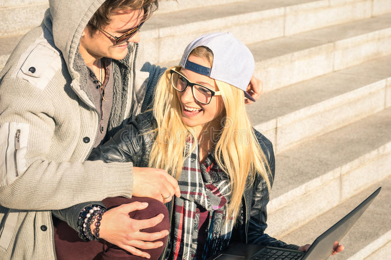 Young hipster happy couple with computer laptop in urban area royalty free stock photos