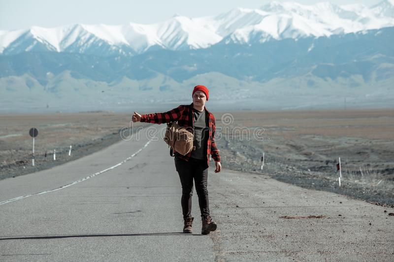 Young hipster hitchhiking on lonesome road with mountains in background. Young hipster dressed in red shirt and red hat hitchhiking on long lonesome road with royalty free stock photography