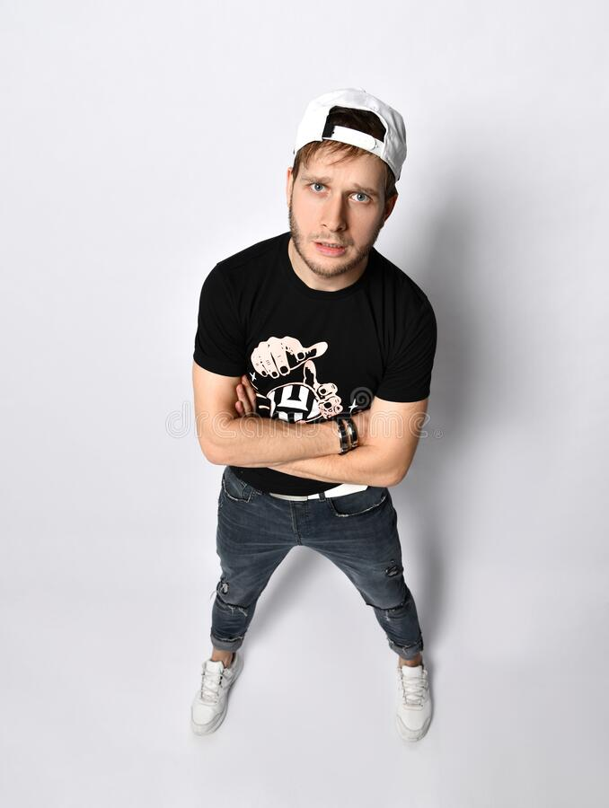 Hipster male in cap, black t-shirt, bracelets, jeans and sneakers. He folded his hands, posing isolated on white. Full length. Young hipster male in cap, black t stock image