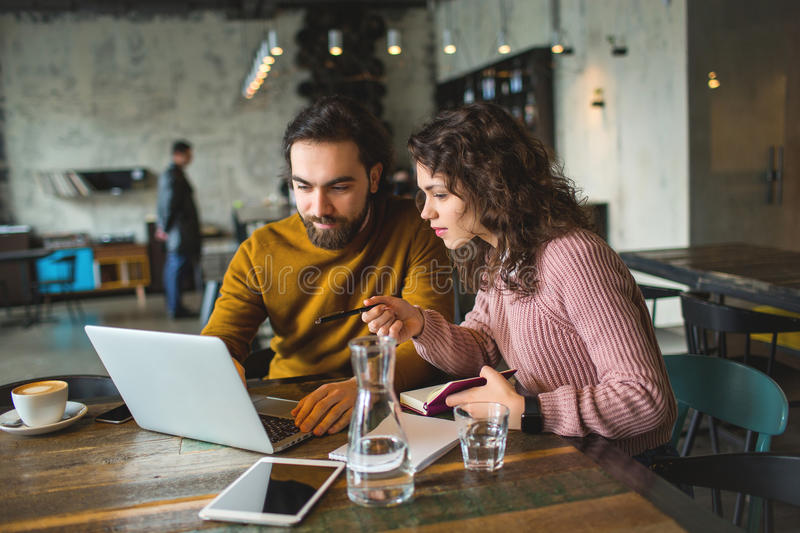Young hipster male and female working laptop together in cafe. Young hipster male and female working with laptop together in trendy cafe stock photography