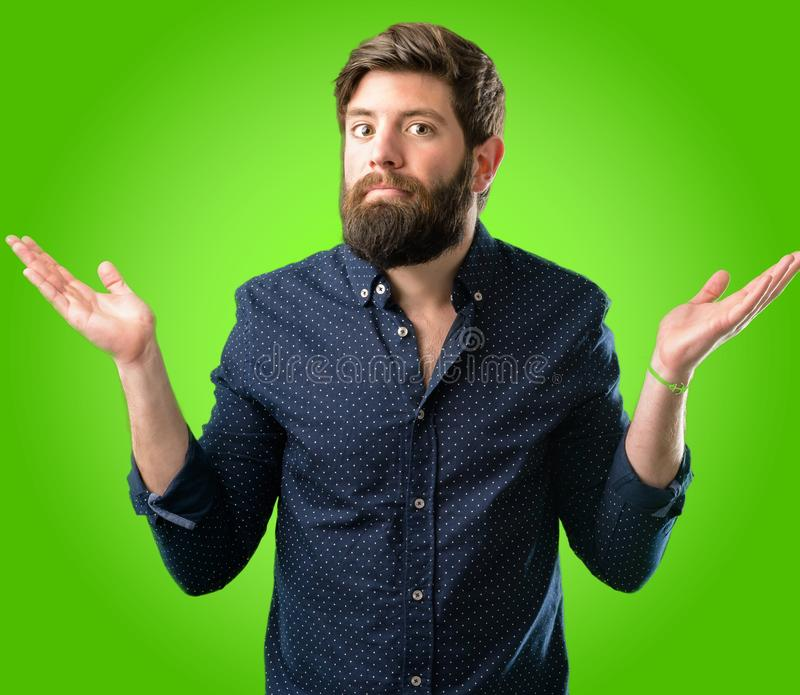 Young hipster man with beard and shirt. Young hipster man with big beard doubt expression, confuse and wonder concept, uncertain future shrugging shoulders over stock images