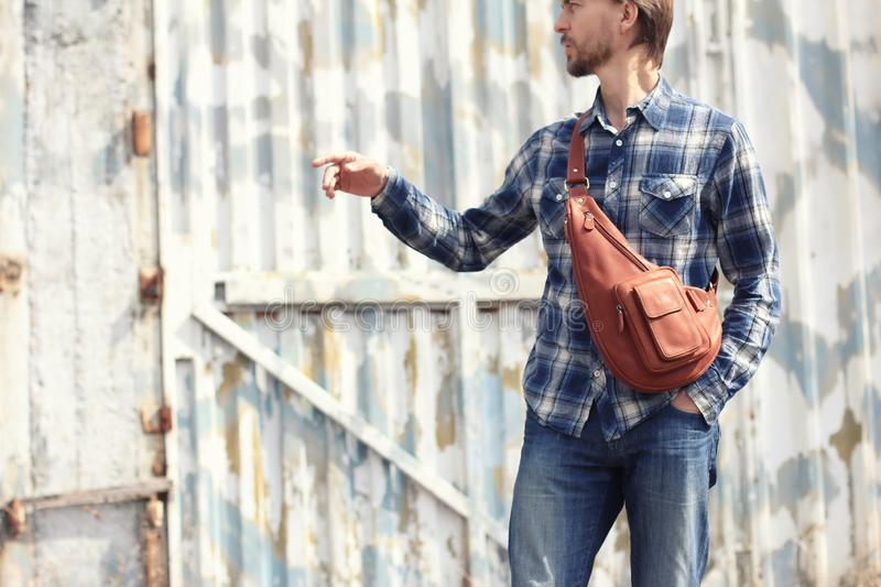 Young hipster man in casual wear with stylish leather backpack, stock images