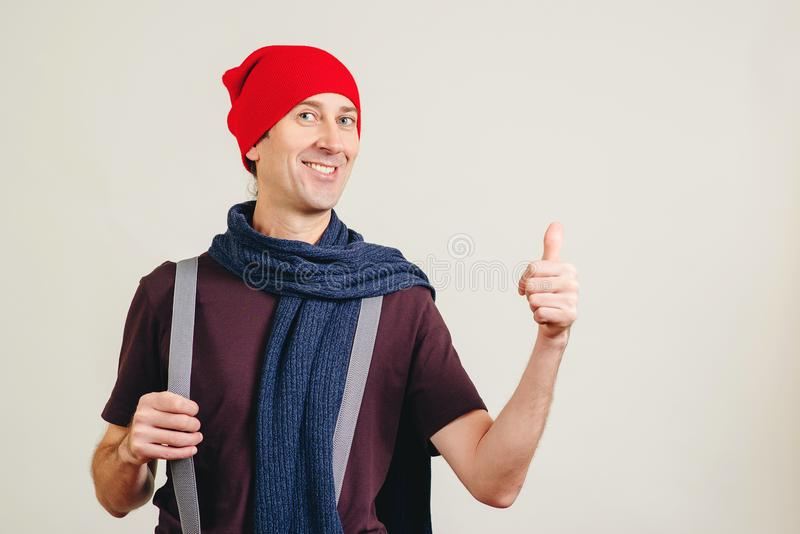 Young hipster man doing happy thumbs up gesture with hand. Funny guy showing success. Emotion and gesturing concept. Man showing stock images