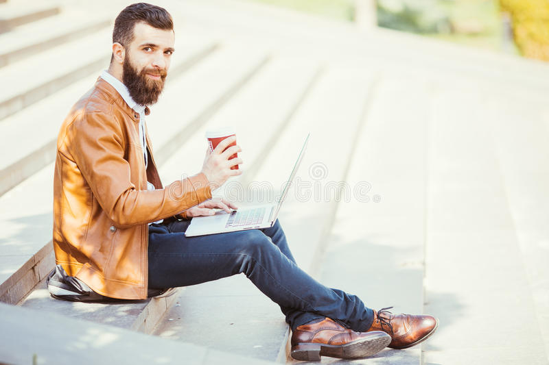 Young hipster man drinking coffee on the street and holding laptop computer in hand. stock image