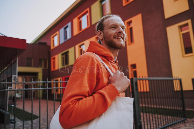 Young hipster man with eco bag on walk. Urban lifestyle concept. Waist up portrait of young happy hipster man in red fleece and with white eco bag walking on royalty free stock image