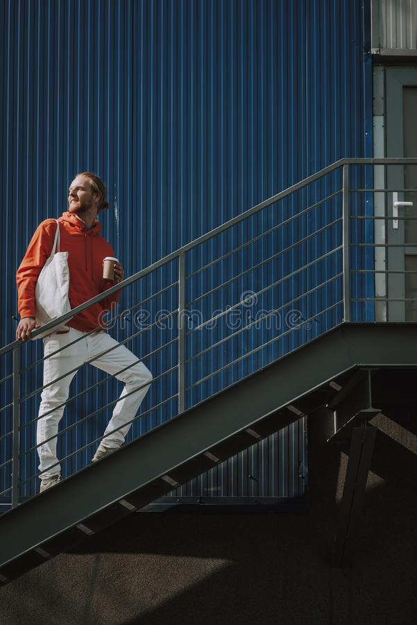 Young hipster man going upstairs with coffee. Urban lifestyle concept. Full length portrait of young smiling red haired hipster man with cup of coffee going royalty free stock photography