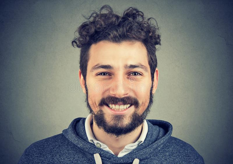 Hipster man in gray hoodie smiling happily at camera. royalty free stock photo