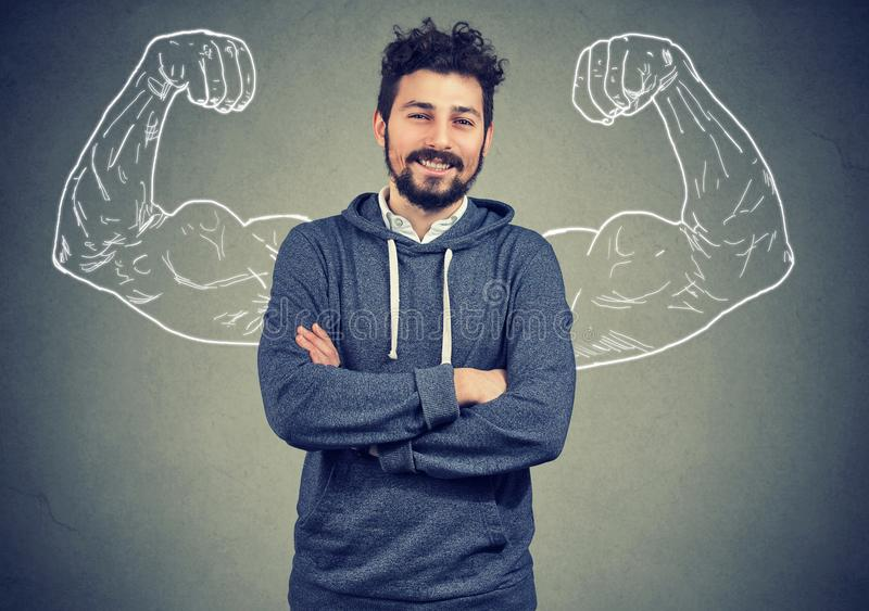 Overconfident man with strong hands. Young hipster man in hoodie standing with painted strong arms on gray background stock images