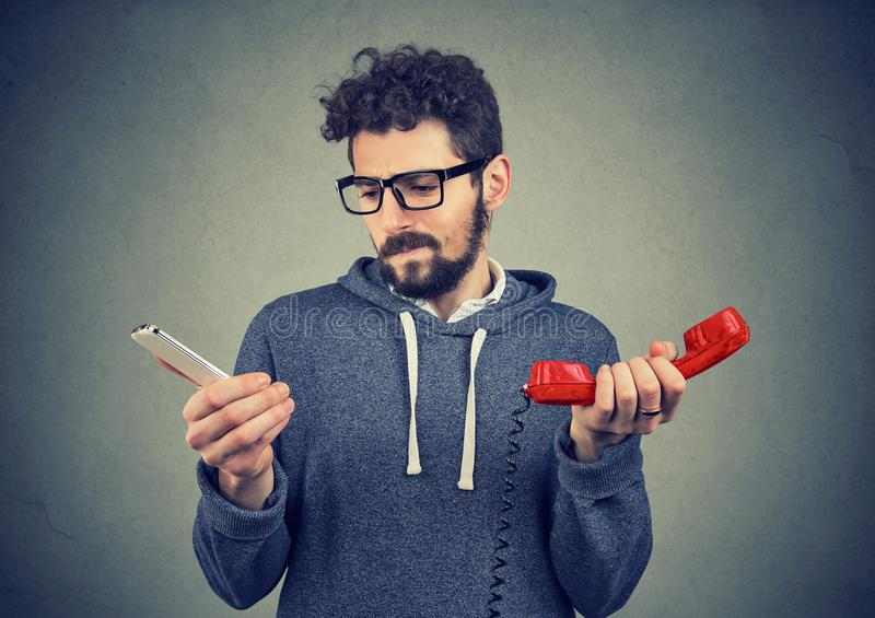 Confused man with old and new phones stock photos