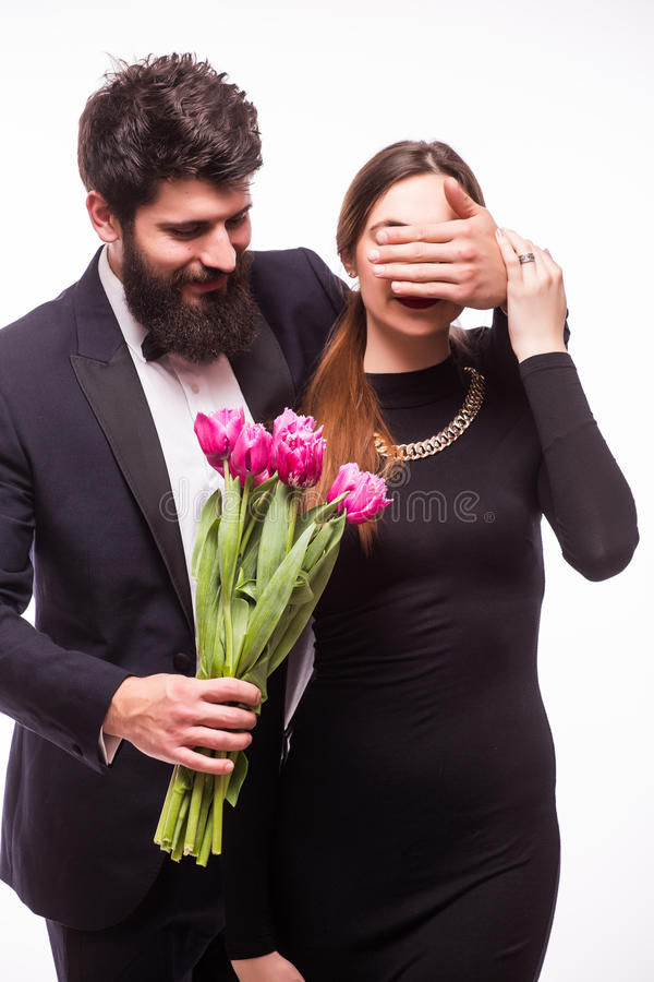 Young hipster man make surprise for his girlfriend and give her a tulips bucket stock photography
