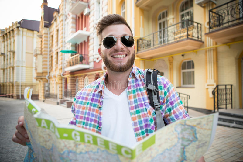 Young hipster man with map. Hipster man examining the map. Happy young tourist in sunglasses smiling and carrying backpack outdoors royalty free stock image