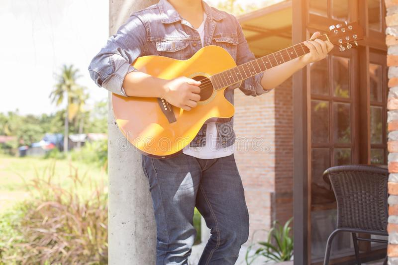 Young hipster man practiced guitar in the park,happy and enjoy playing guitar. royalty free stock photo