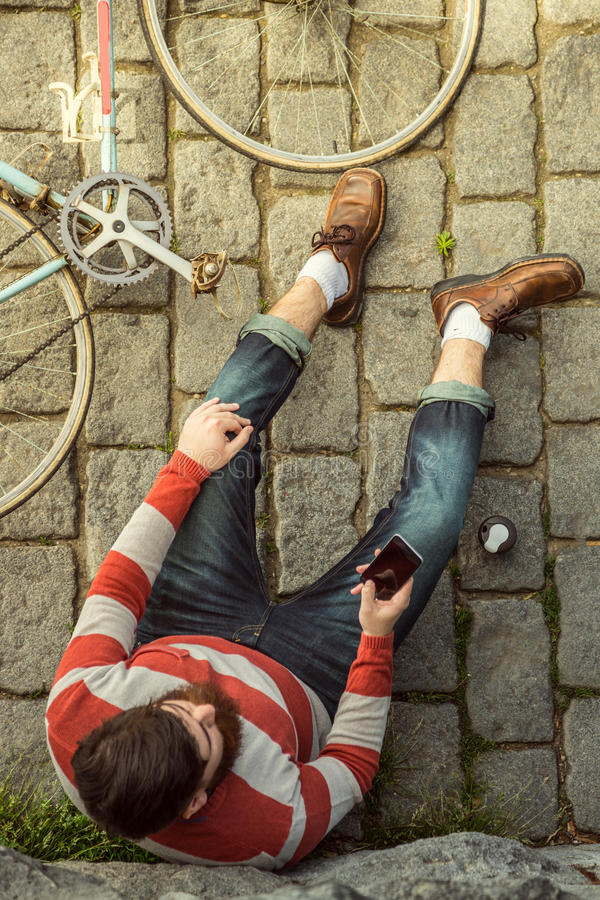 Young hipster man sitting and using cellphone stock image