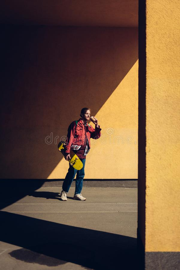 Young hipster man with skateboard and coffee. Urban lifestyle and activity. Full length portrait of young smiling hipster guy walking outdoor with yellow stock photos