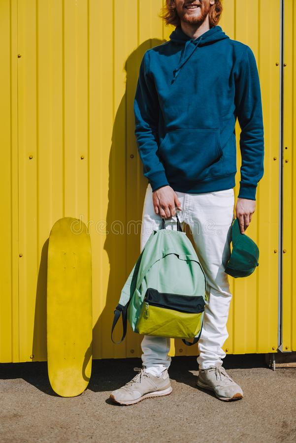 Young hipster man with skateboard and sack. Urban lifestyle and activity. Cropped head portrait of young hipster guy with sack and skateboard staying on yellow royalty free stock photo