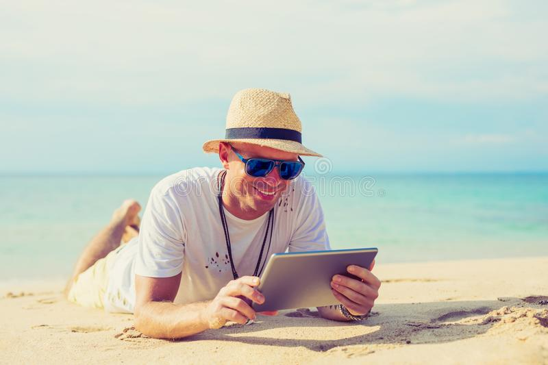 Young handsome man using tablet on the beach royalty free stock images